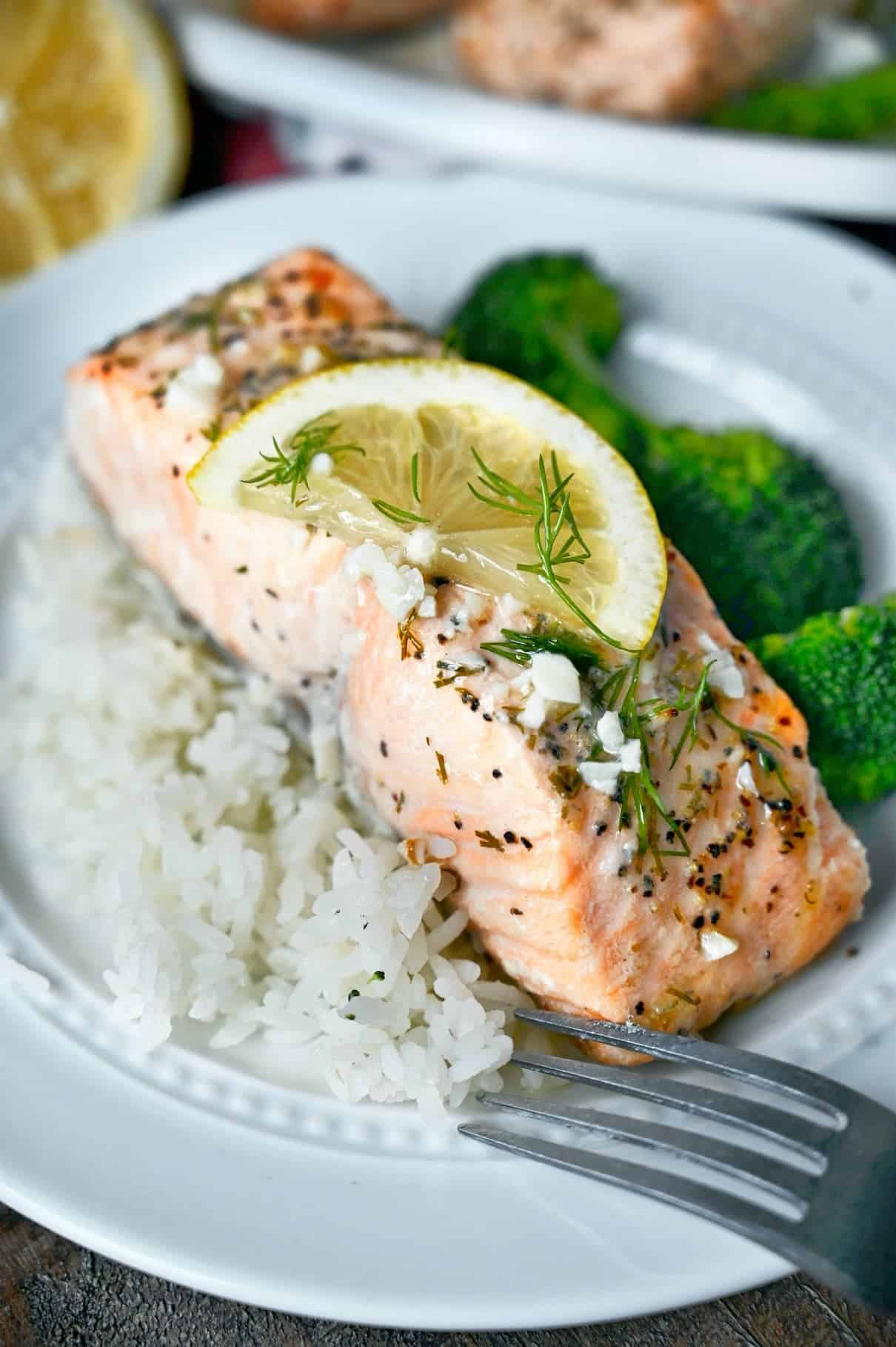 A salmon filet on a plate with a side of white rice and broccoli. Lemon butter sauce on top with a lemon slice.