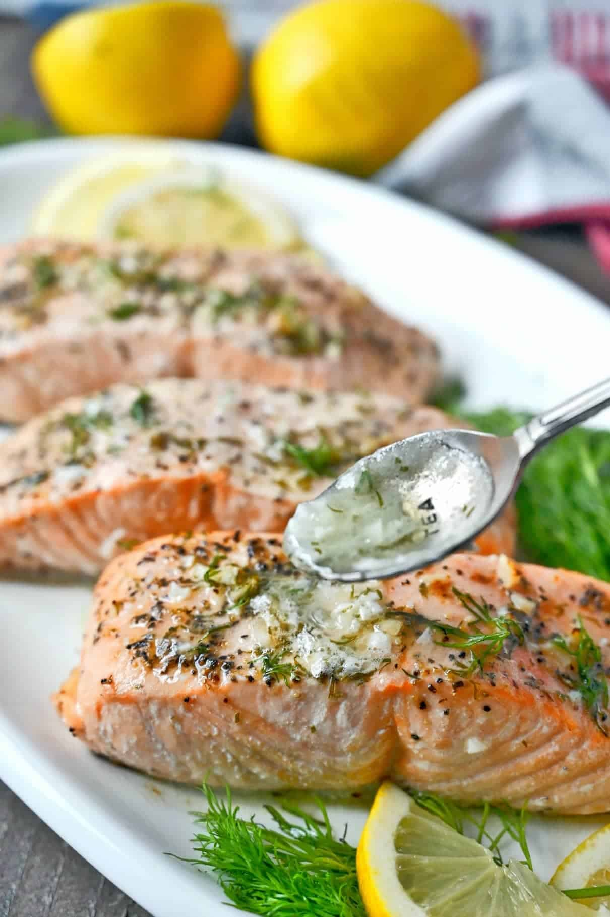 Three salmon filets on a white platter and a spoon pouring on lemon butter sauce.
