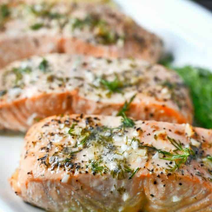 Three salmon filets on a white platter with lemon butter sauce on top.