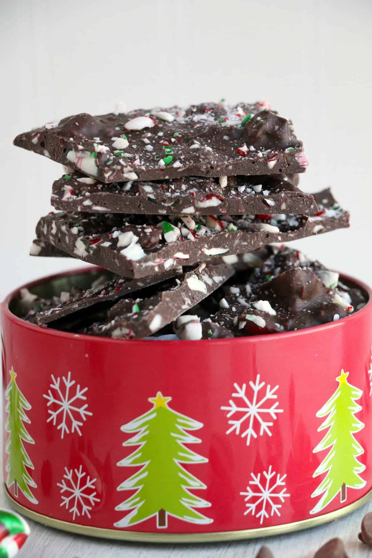 Chocolate peppermint bark stacked on top of each other in a christmas tin.