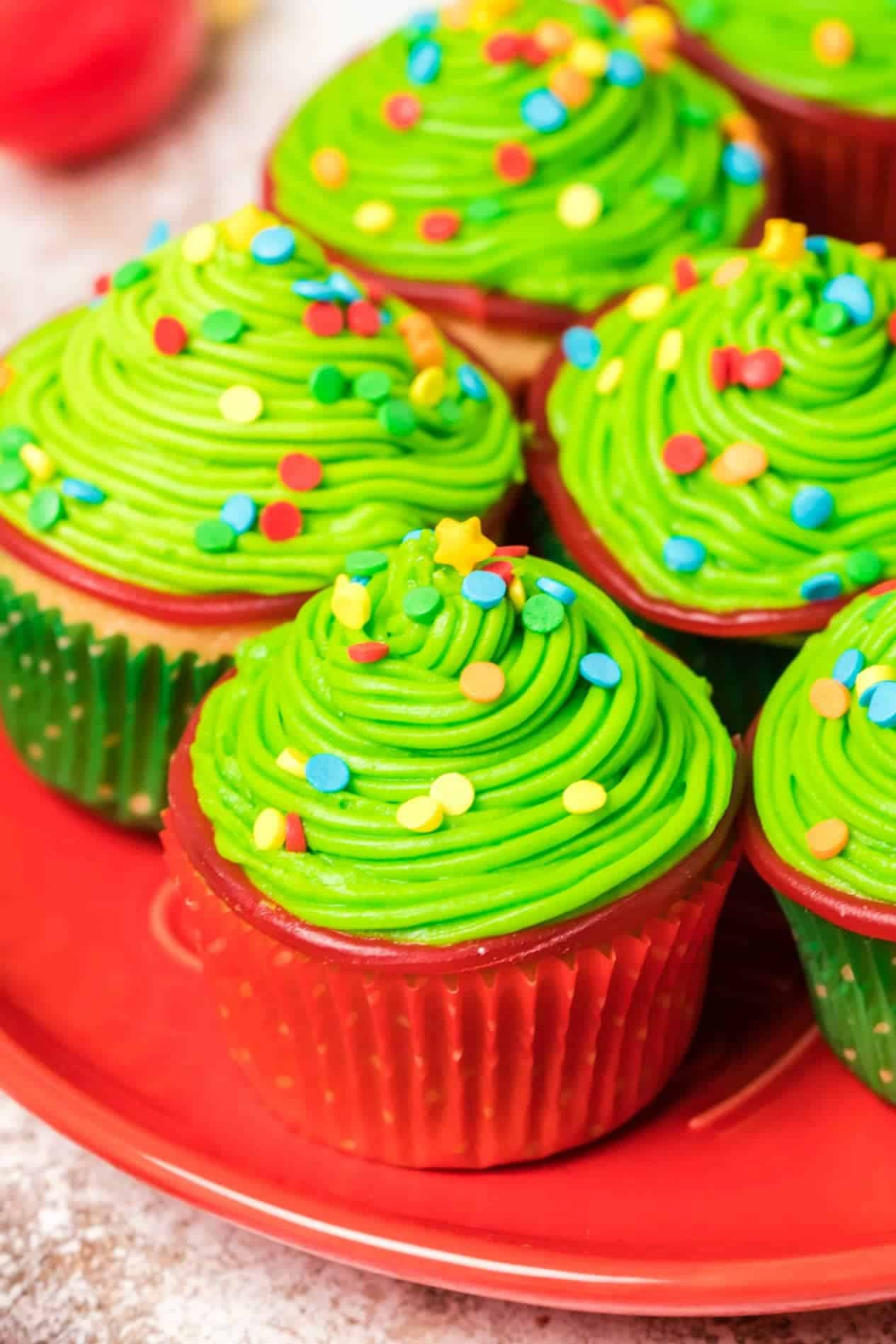 Christmas tree cupcakes on a red platter.