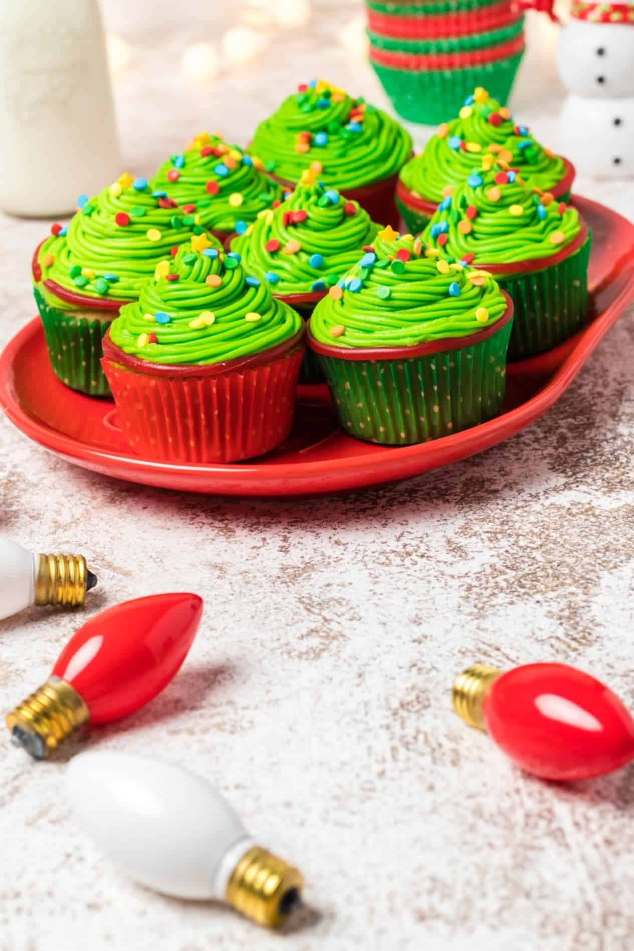 Christmas tree cupcakes on a red platter with christmas lights scattered around.