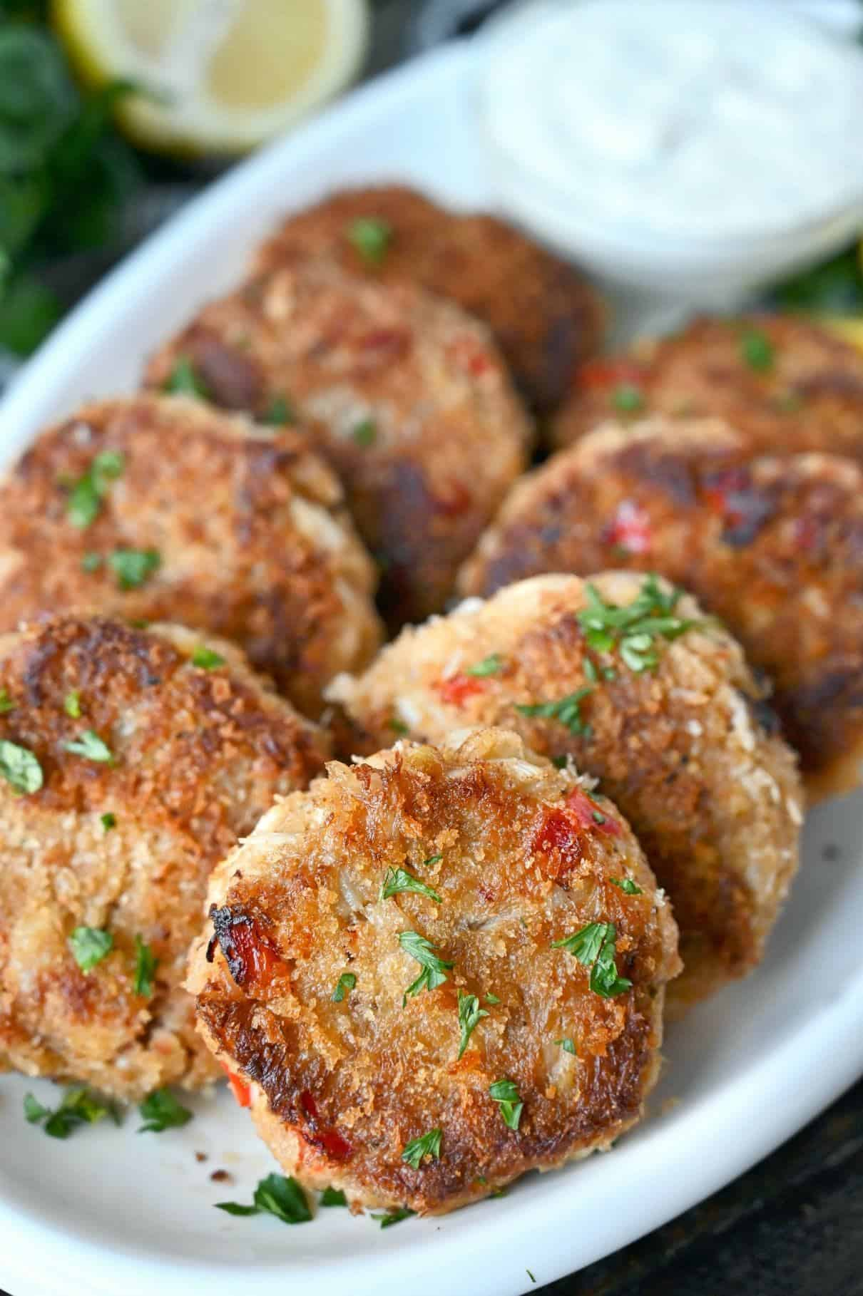 Crab cakes on a white platter.