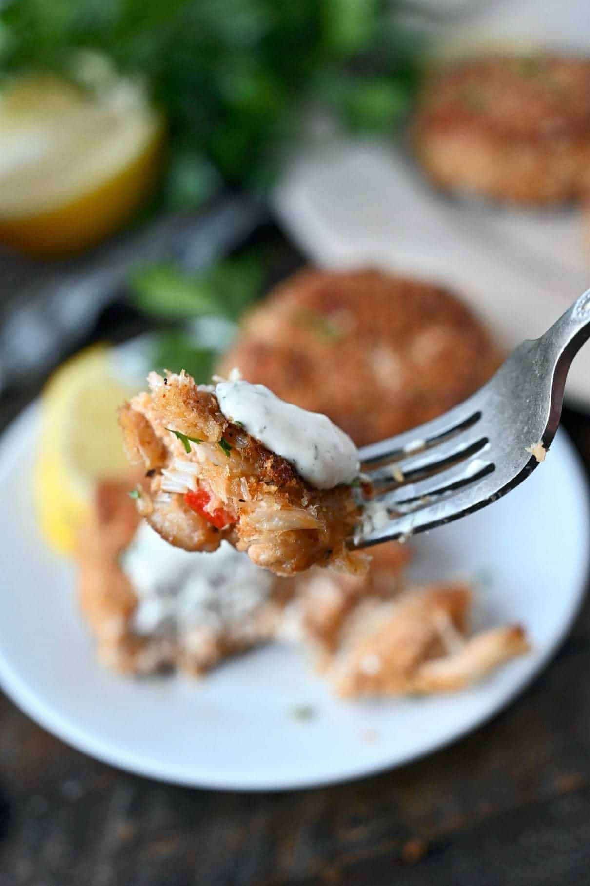 A bite of crab cake and a dollop of lemon dill sauce on a fork.