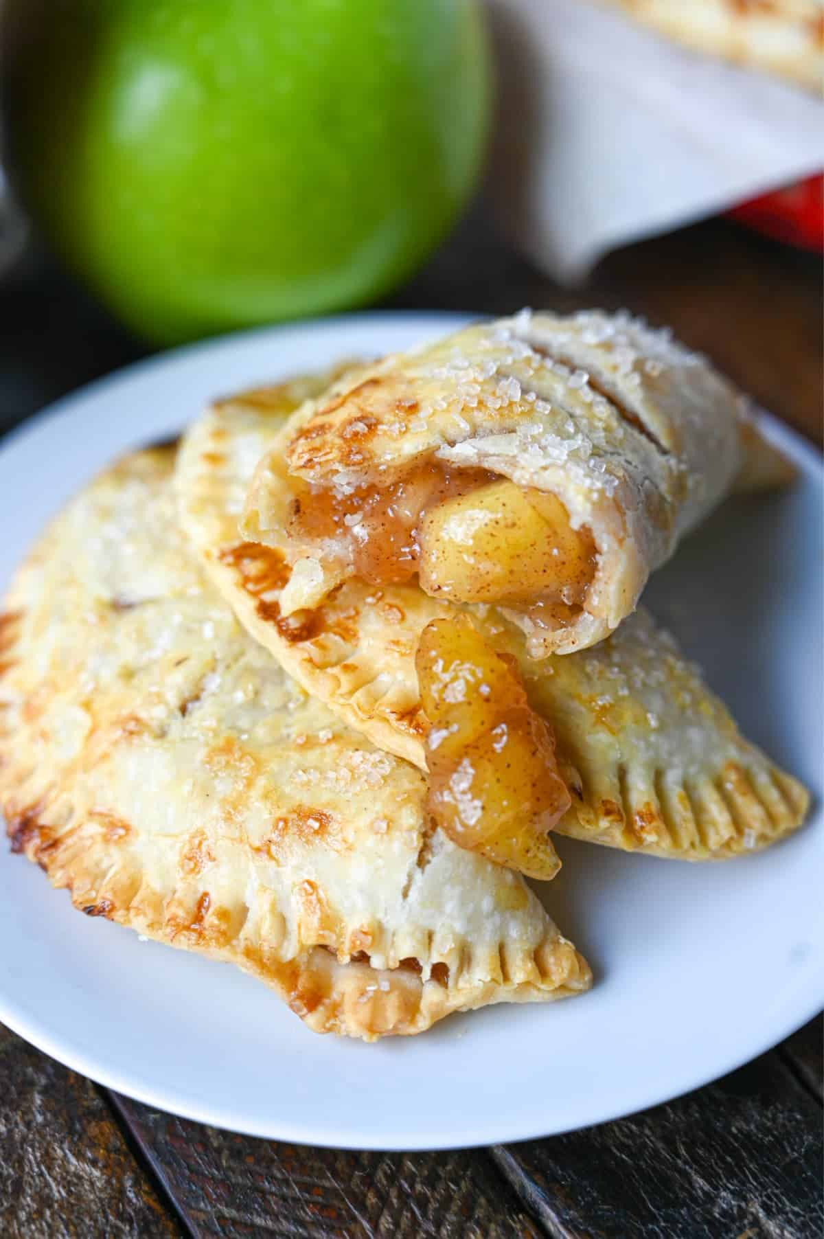 Apple hand pie with a bit out of it piled on top of two other hand pies on a white plate.