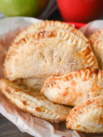 Close up photo of several different hand pies in a red plastic basket.