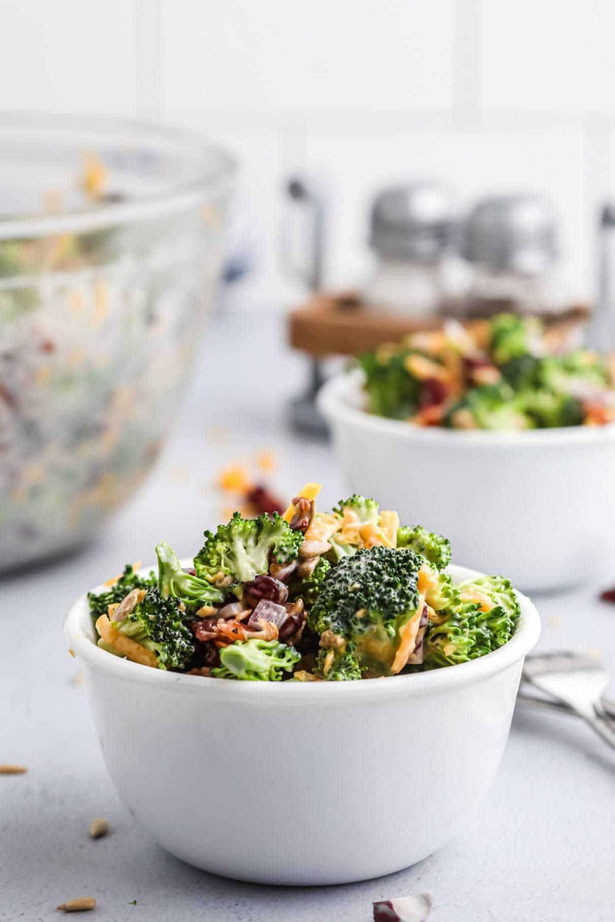 Broccoli salad in a white salad bowl.