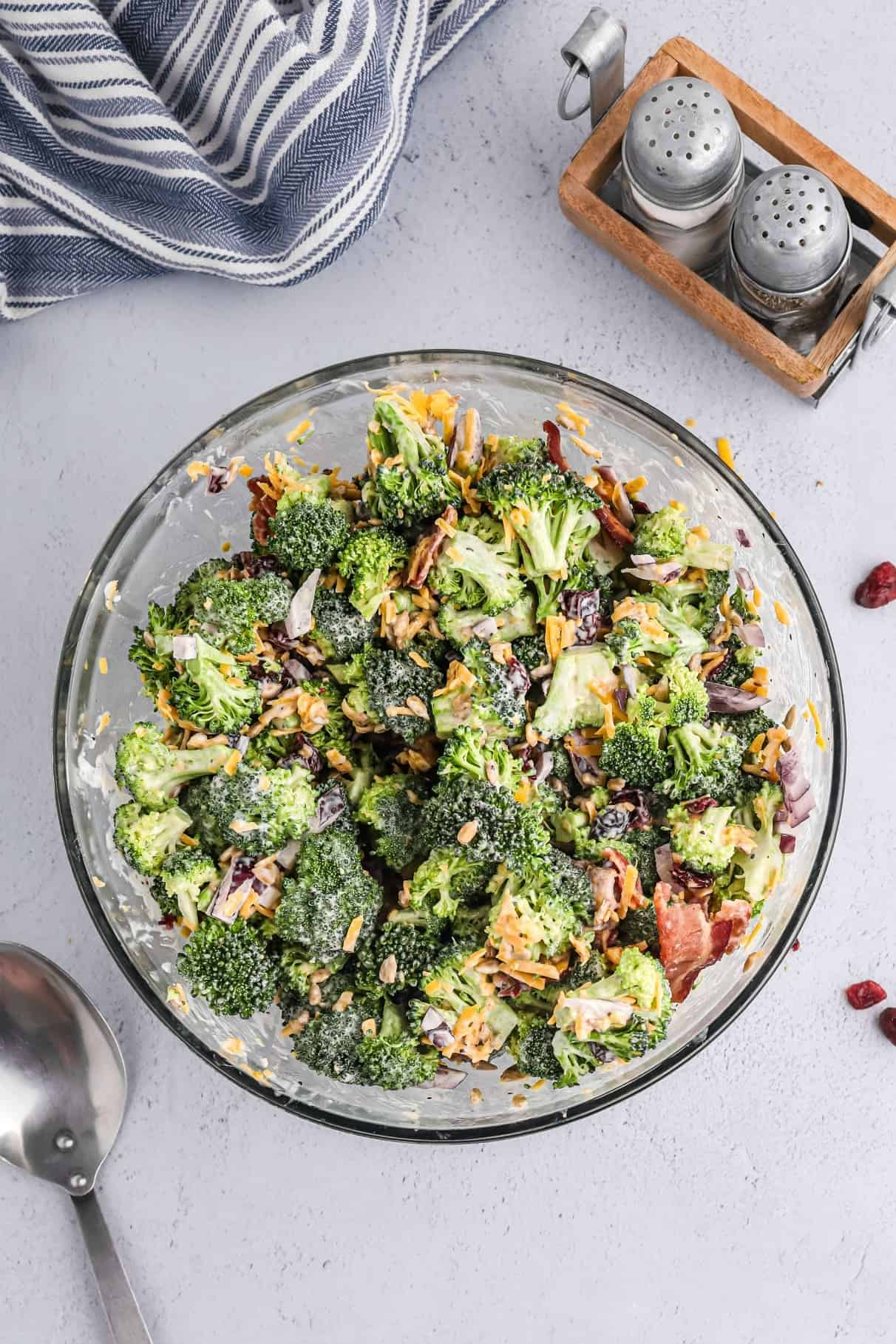 Broccoli salad in a clear glass bowl.