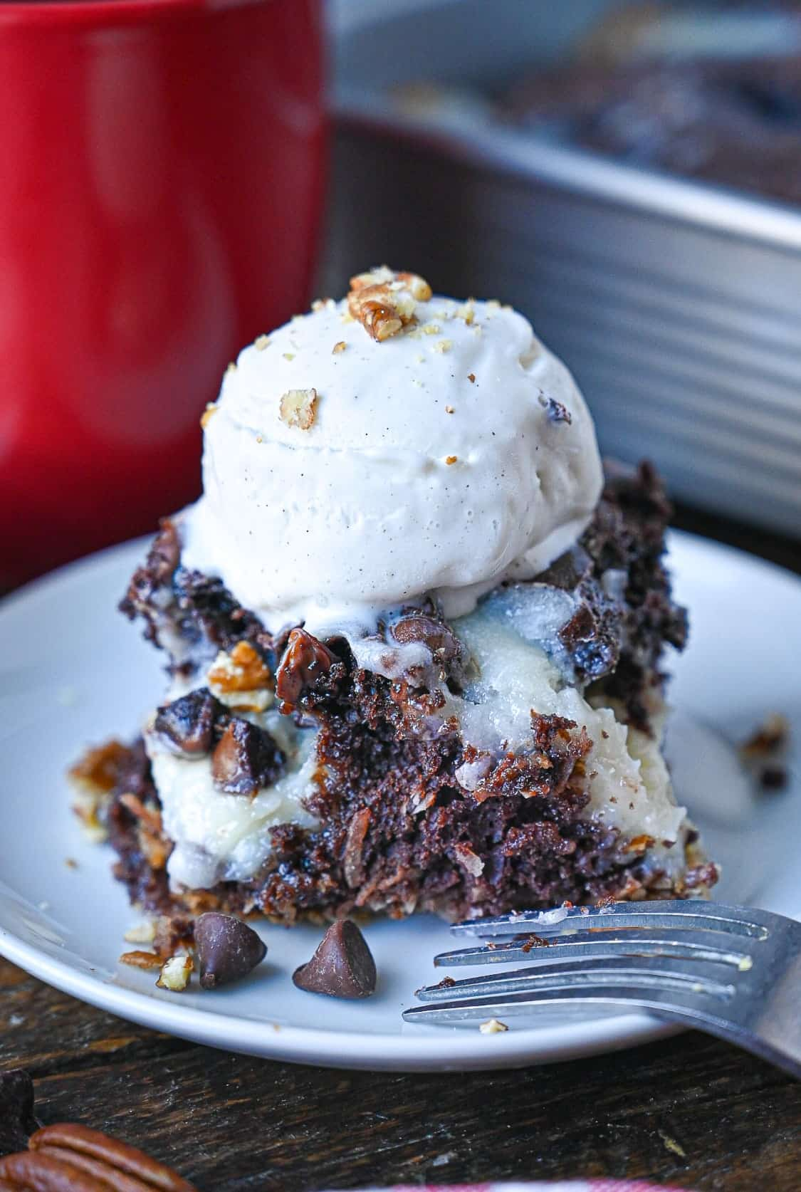 A piece of chocolate earthquake cake on a white plate with a scoop of vanilla ice cream on top.