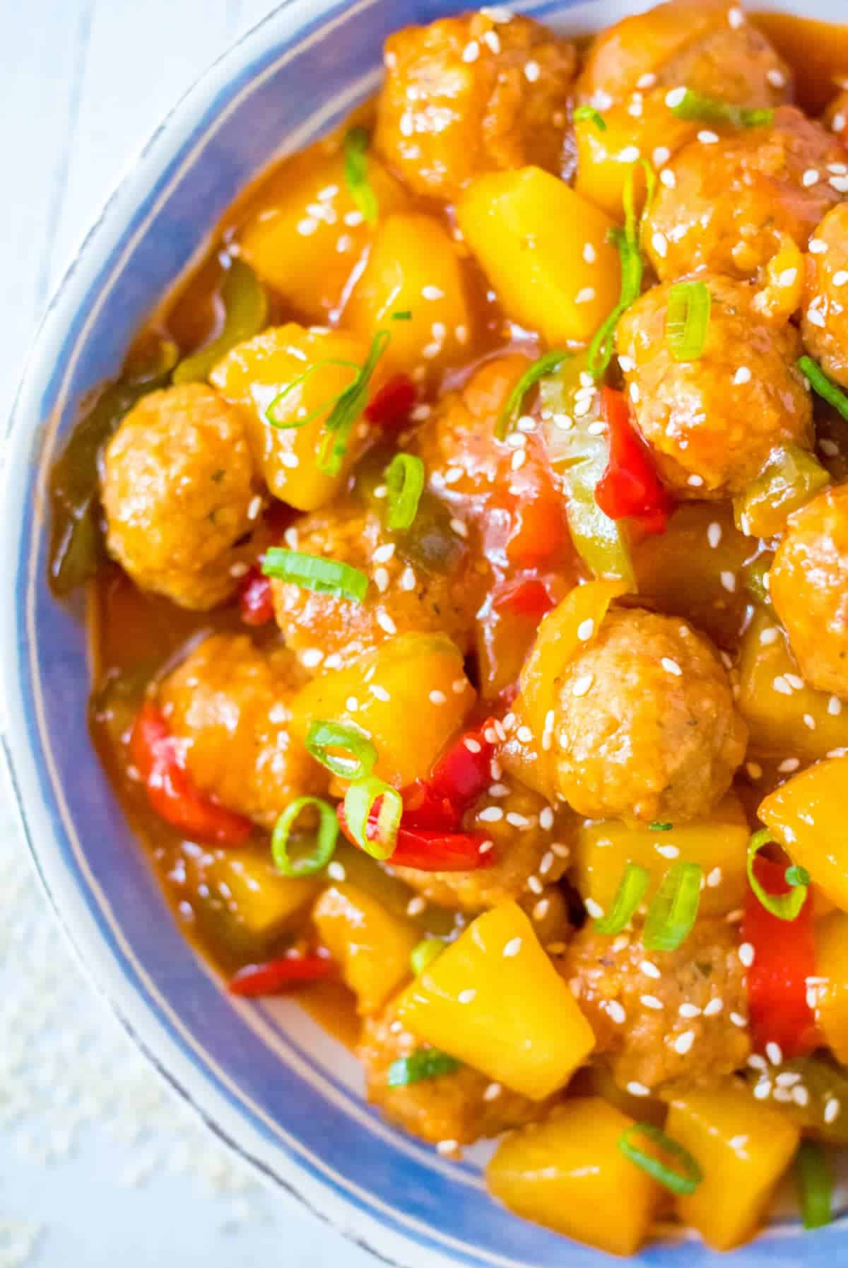 Sweet and sour meatballs in a bowl with pinapple and red peppers. Sesame seeds sprinkled on top.