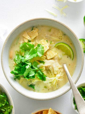 Close up photo of white chicken in a white bowl with tortilla chips, cilantro and a lime slice on top.