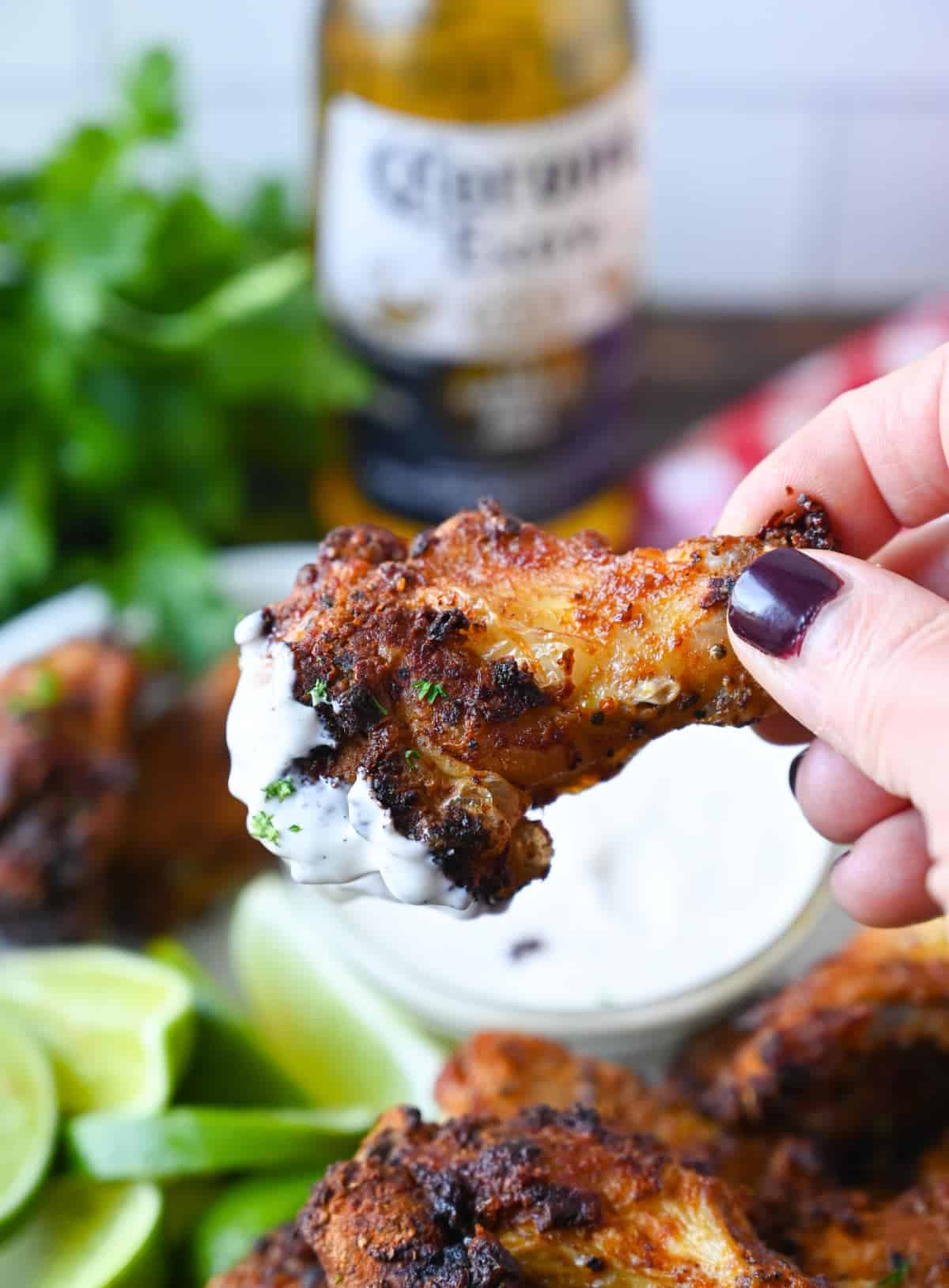 A chicken wing being picked up and that has been dipped in ranch dressing.