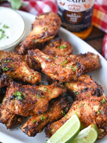 Close up photo of air fryer old bay chicken wings with a side of ranch dressing.