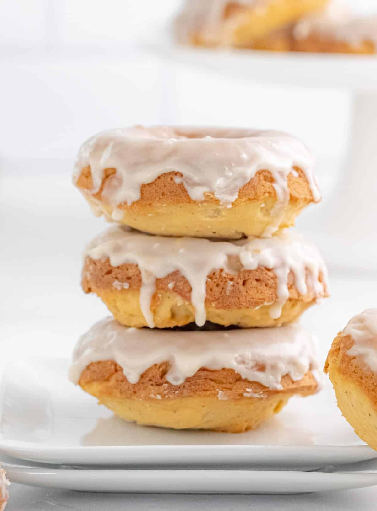 Three baked glazed donuts stacked on top of each other.
