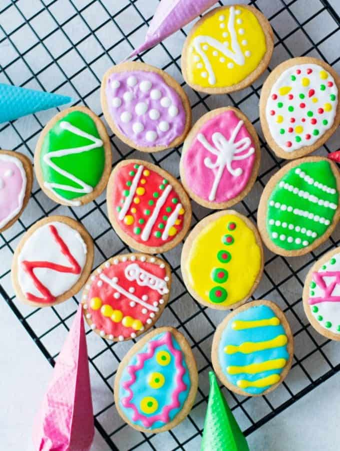 Easter egg cookies that have been decorated and laying on a cooling rack