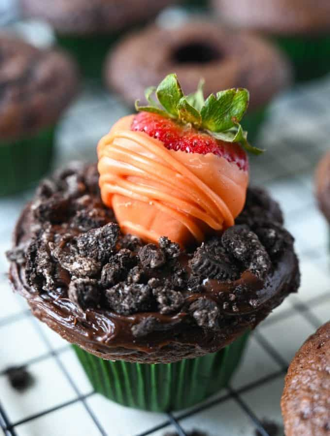 Chocolate dipped strawberry that looks like a carrot on top of a chocolate frosted cupcake with oreo crumbles on top to look like dirt.