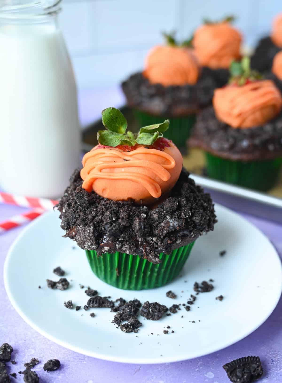 O cupcake de ciocolată cu firimituri de oreo deasupra și o căpșună acoperită cu ciocolată deasupra pentru a semăna cu un morcov.