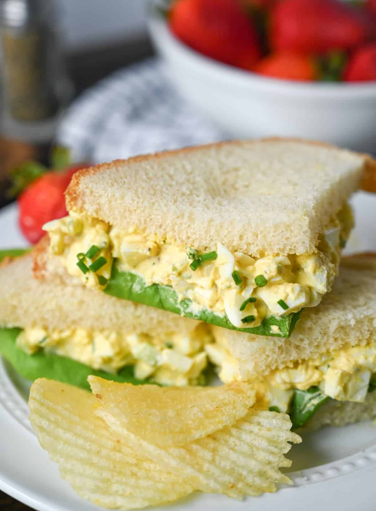 Small cut egg salad sandwiches stacked on top of each other.
