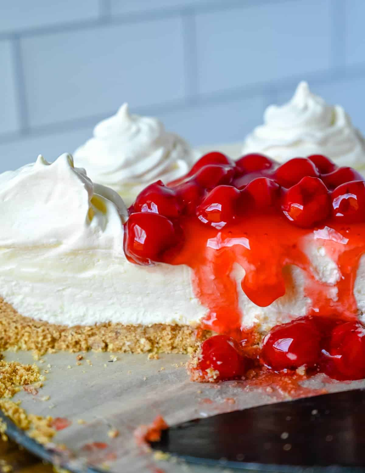No bake cheese cake cut in half with cherries on top.