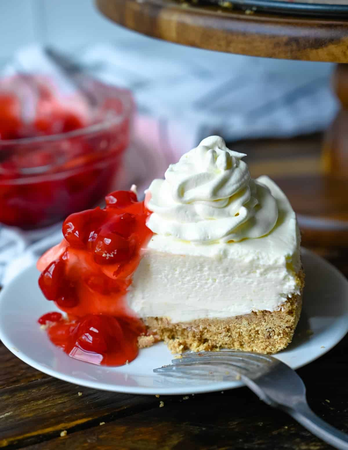 A slice of cheesecake on a small white plate with whipped cream and cherries on top.