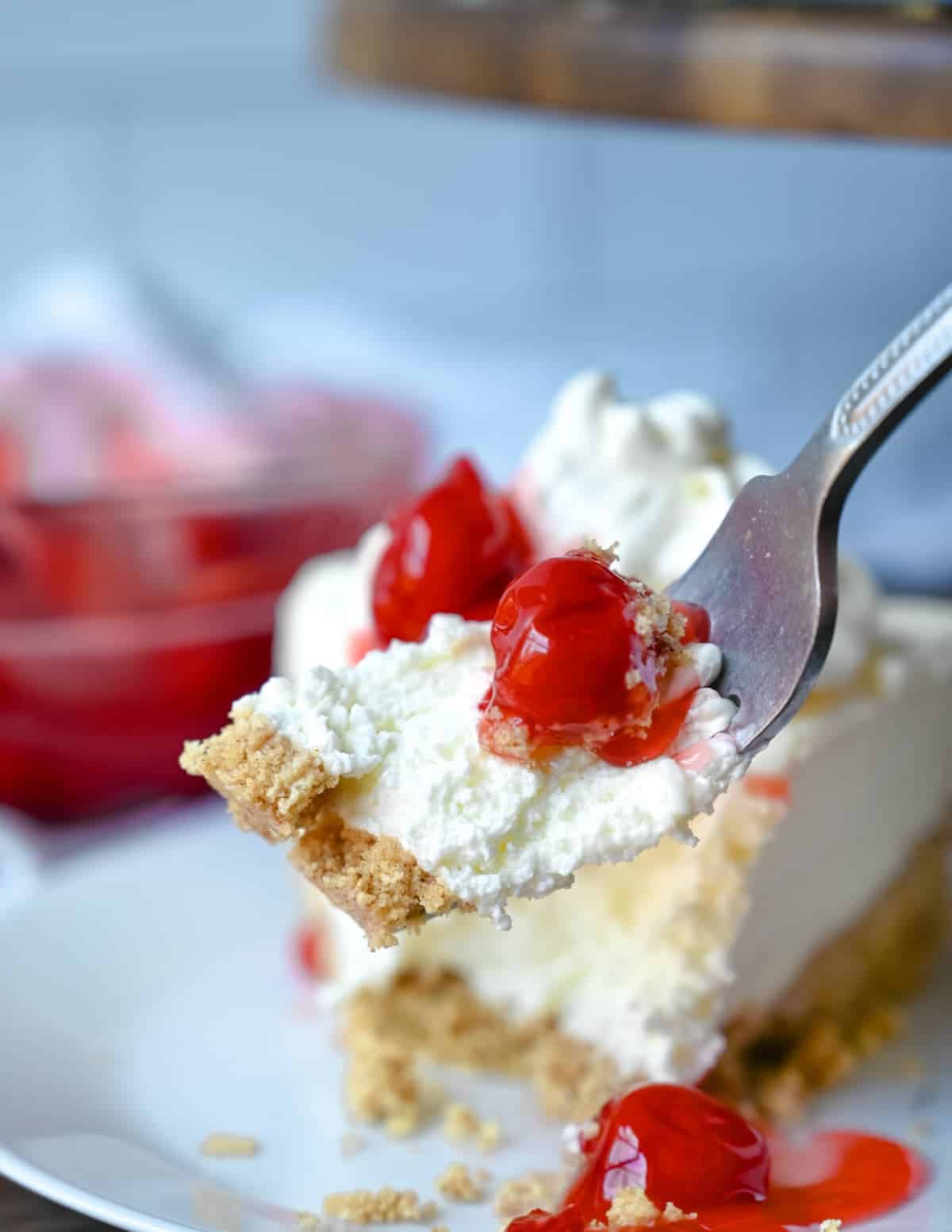 A fork picking up a bite of no bake cheesecake.