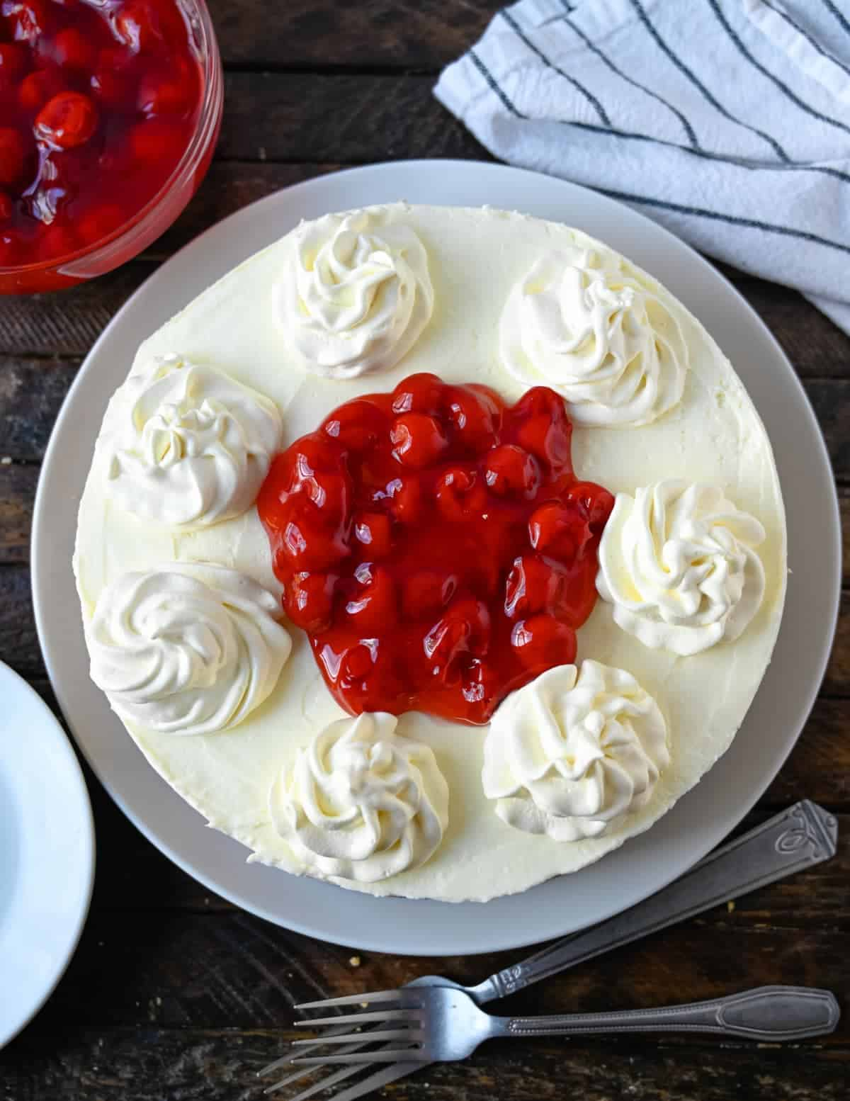 A whole no bake cheesecake with whipped cream and cherries on top.