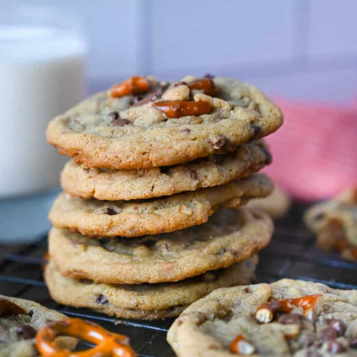 A stack of cookies with a glass of milk in the background.