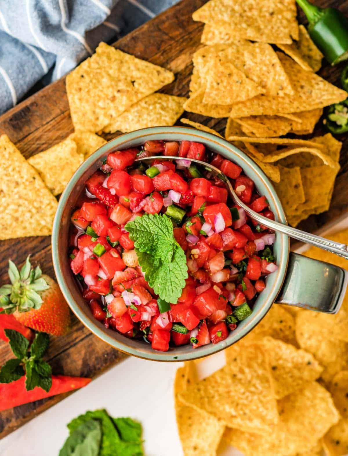 Watermelon salsa in a bowl with tortilla chips placed all around it.