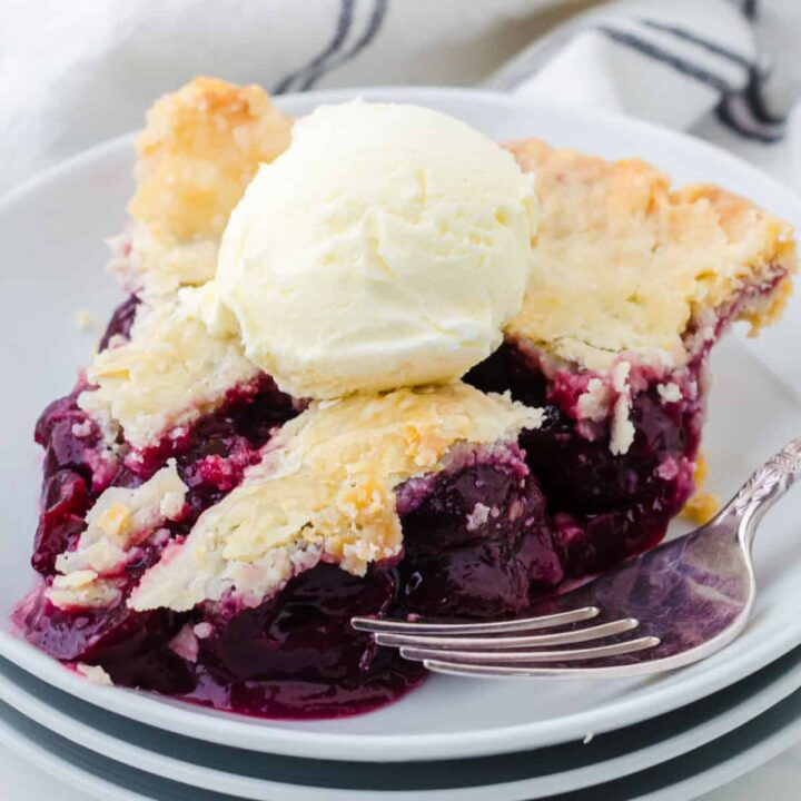 A slice of cherry pie on a white plate with a scoop of vanilla ice cream.