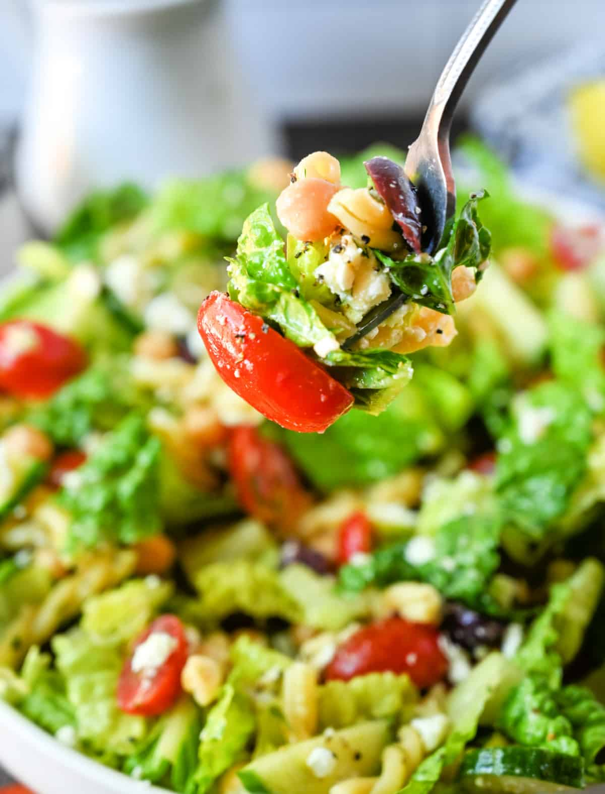 Chopped greek salad bite picked up with a fork.