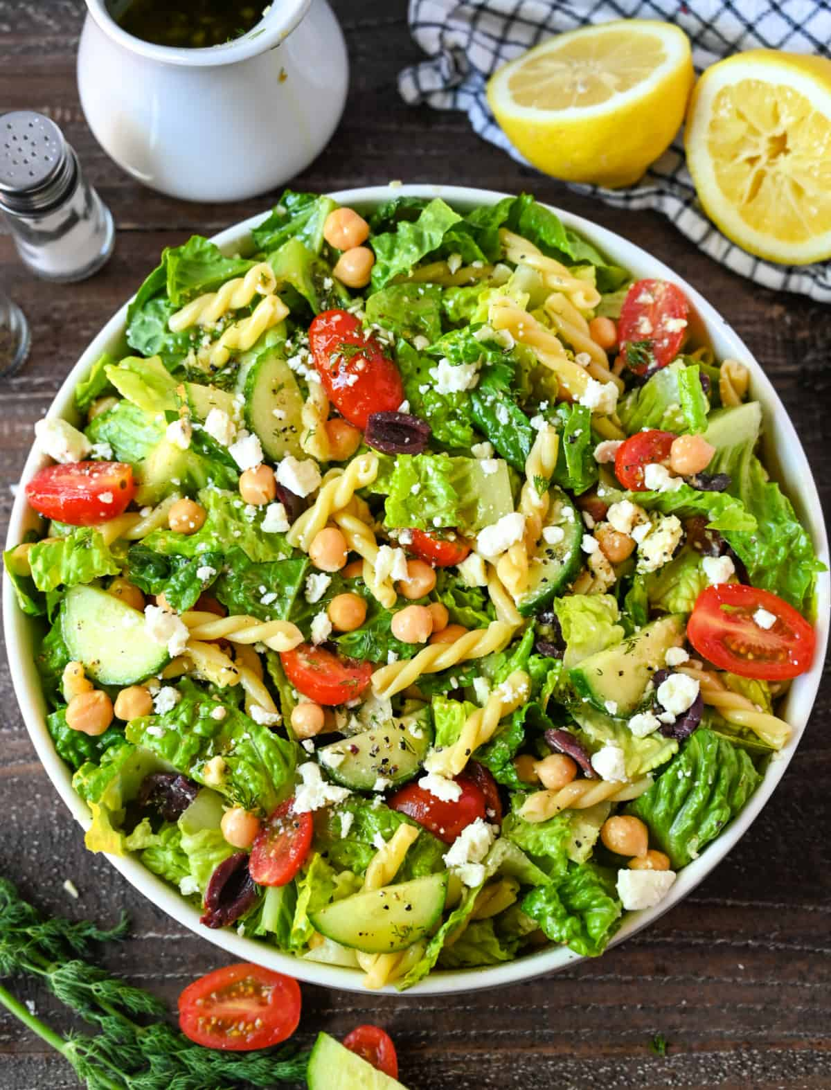 Chopped greek salad with vinaigrette all tossed together in a large white bowl.