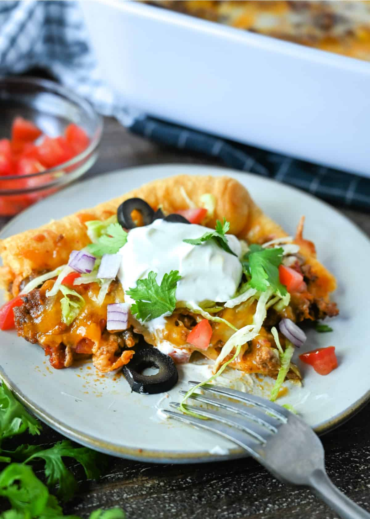 A serving of taco crescent roll bake on a white plate with tomatoes, olives lettuce and sour cream.