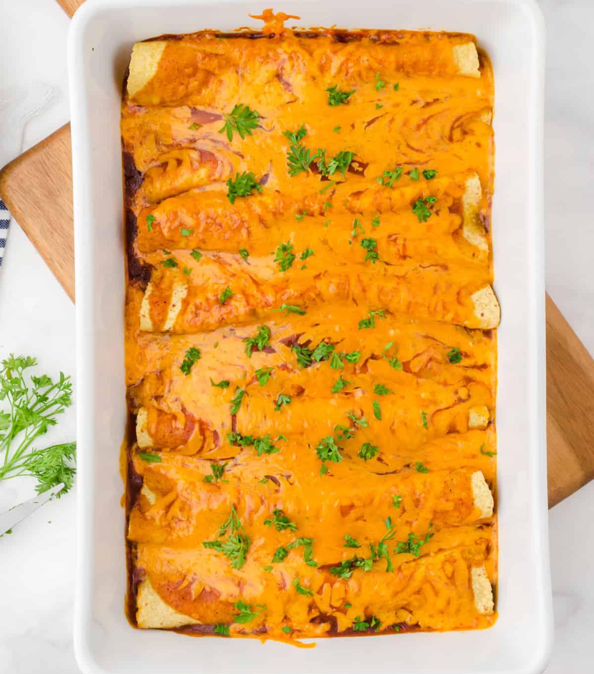 Enchiladas înfășurate și așezate într-un vas de copt alb cu sos enchilada și brânză deasupra și coapte.