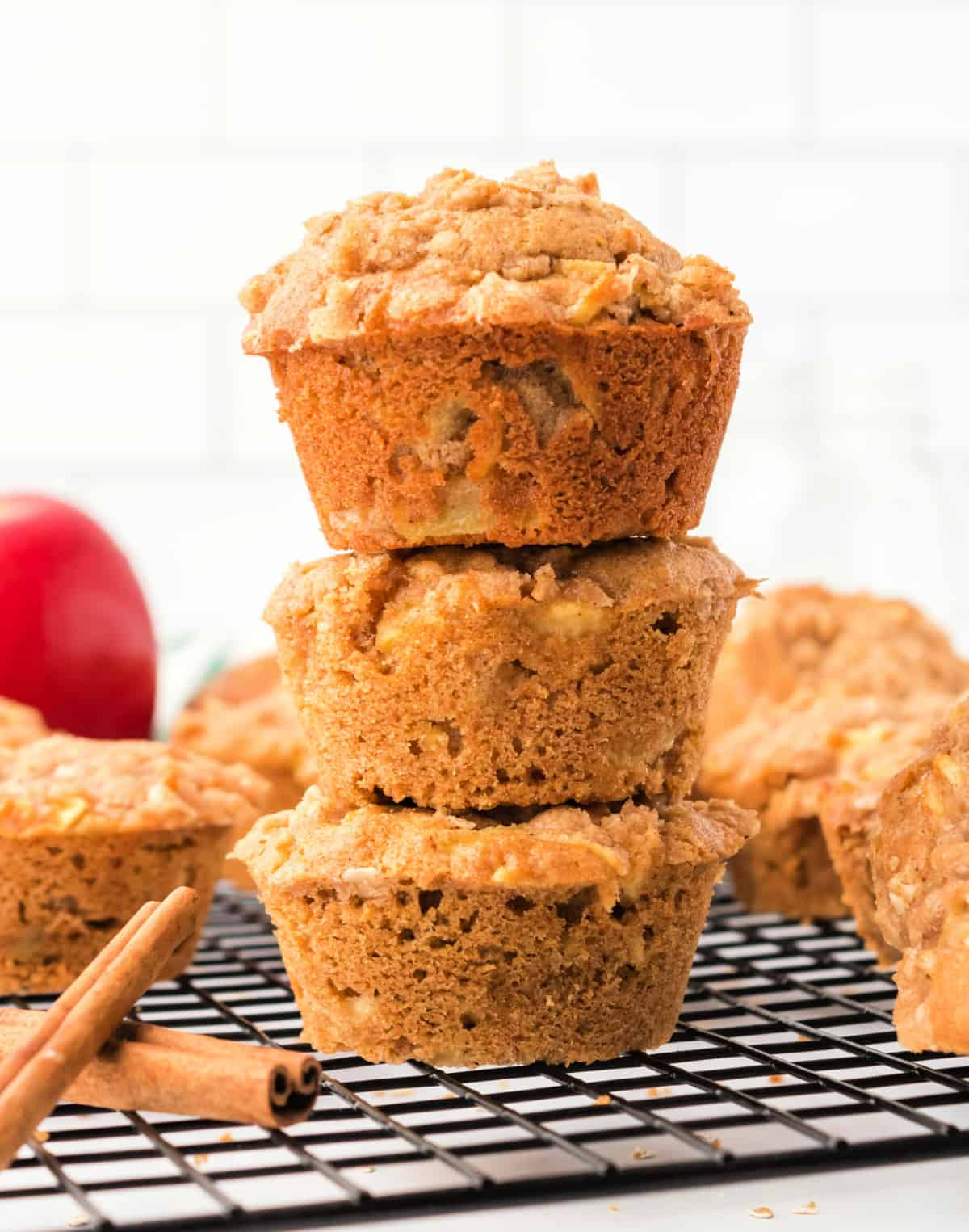 Three apple spice muffins stacked on top of each other.