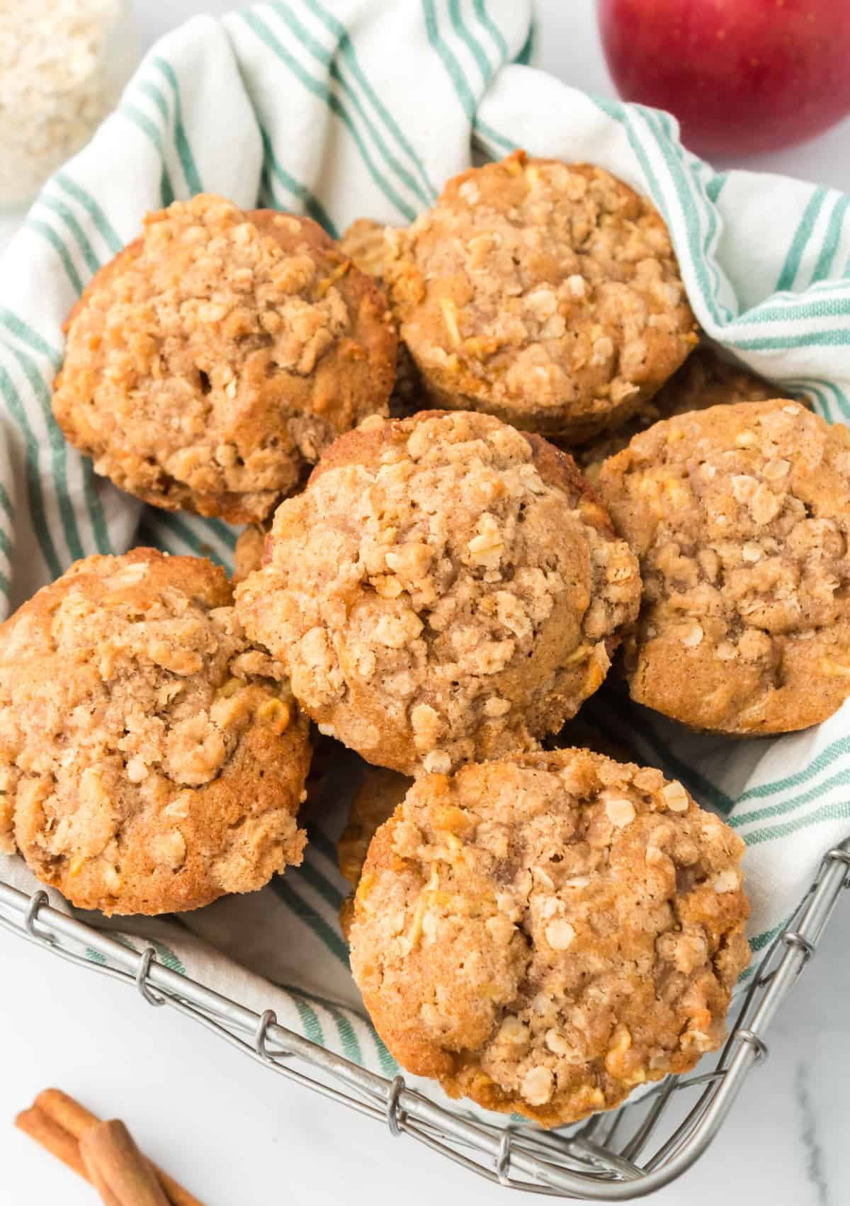 A pile of apple cinnamon muffins in a basket.