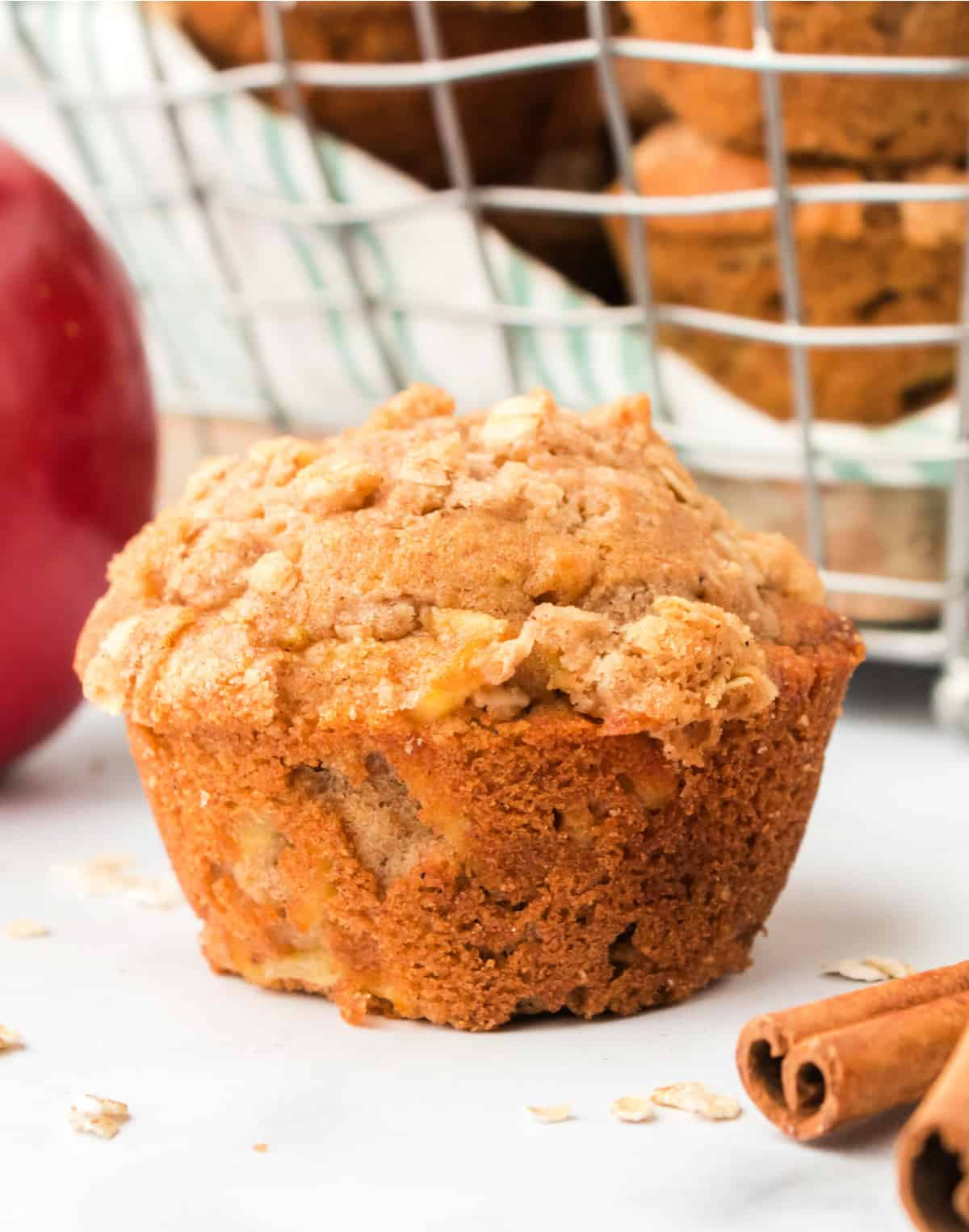 Apple cinnamon muffin with a red apple in the back ground,