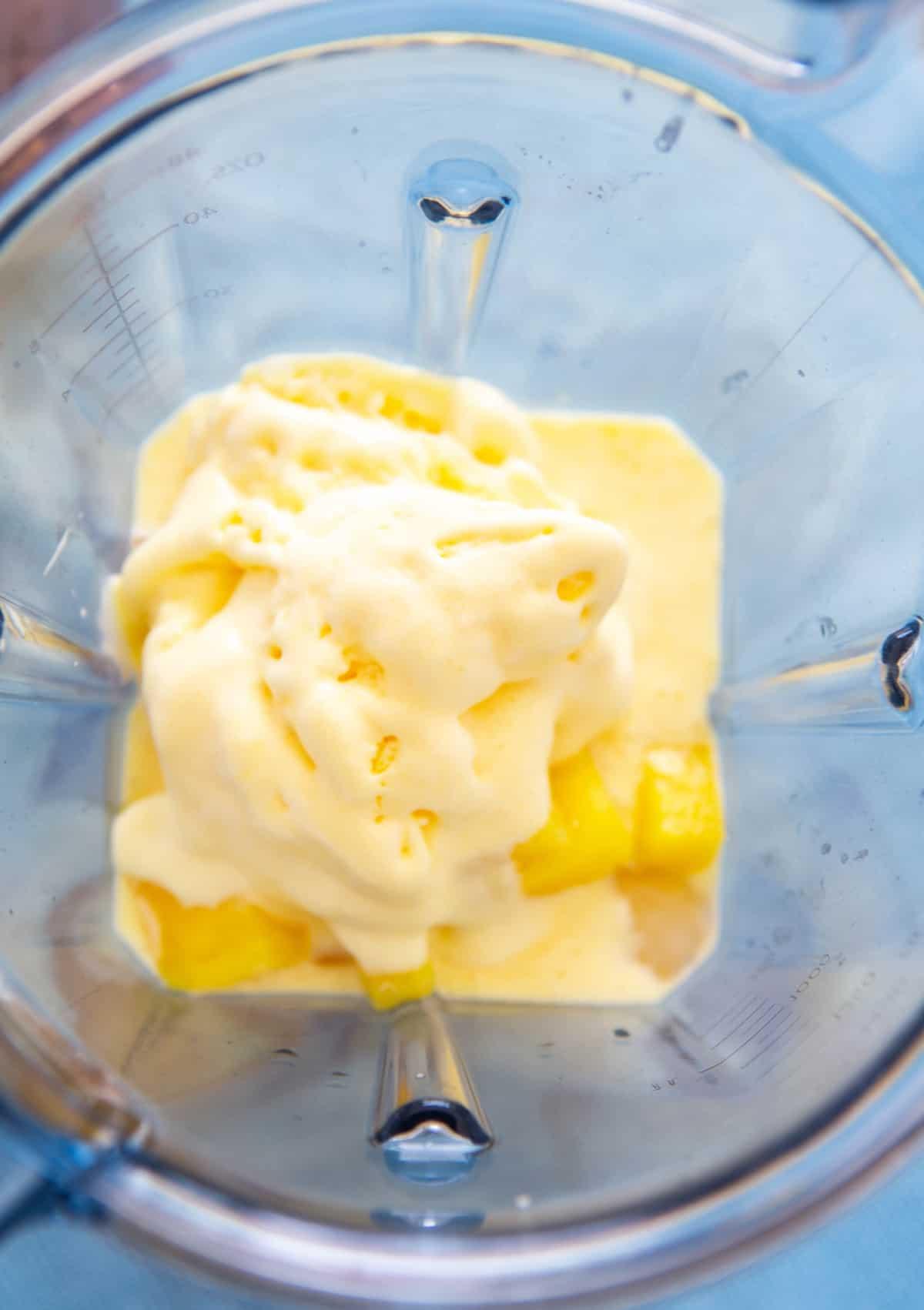 Ananas congelat și înghețată și suc așezat într-un blender.