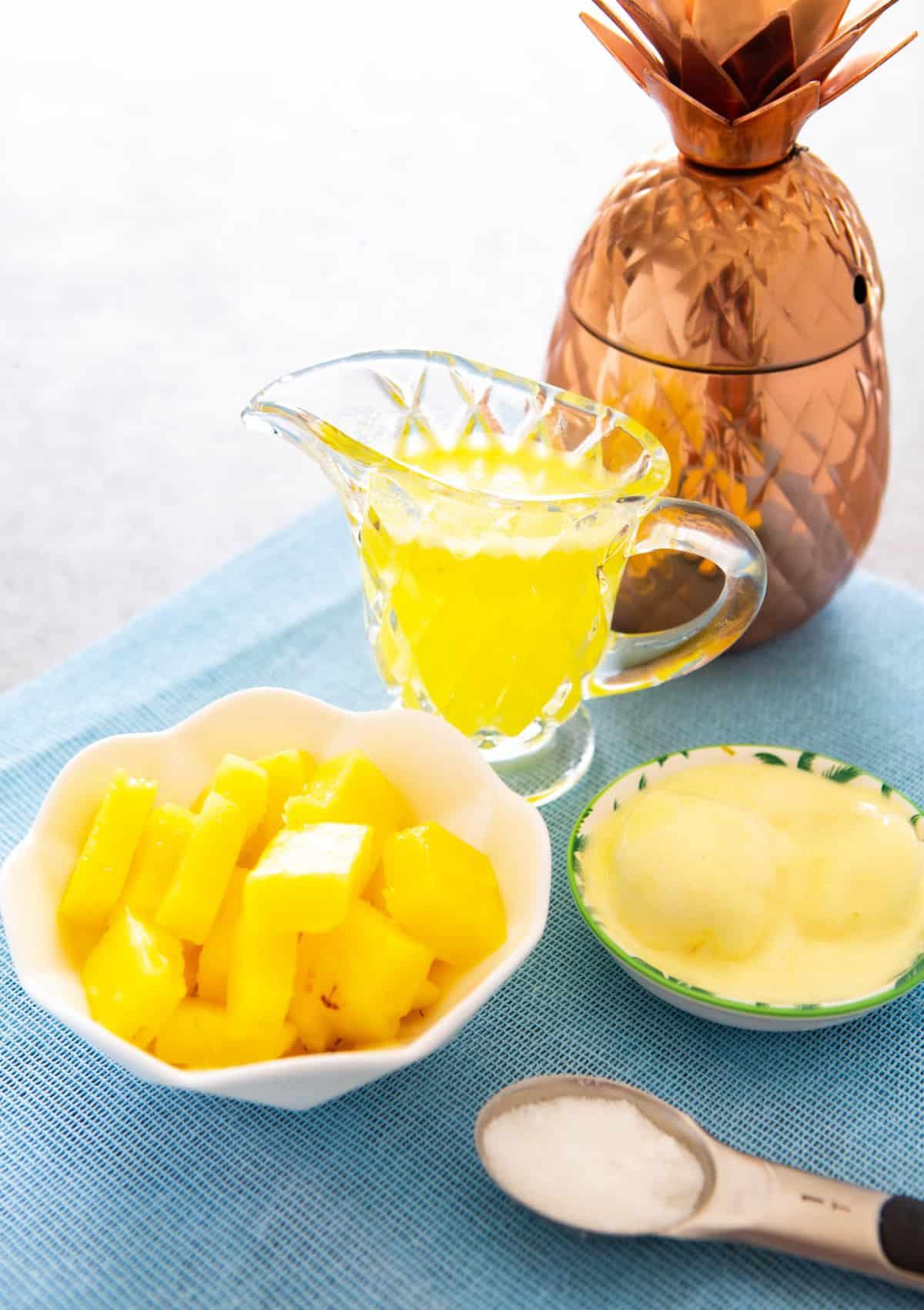 Ananas congelat într-un castron, suc într-un ulcior și înghețată de vanilie, toate așezate pe o masă.