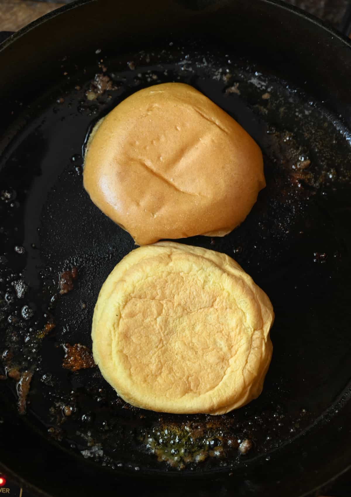 Two brioche buns face down in a hot skillet.