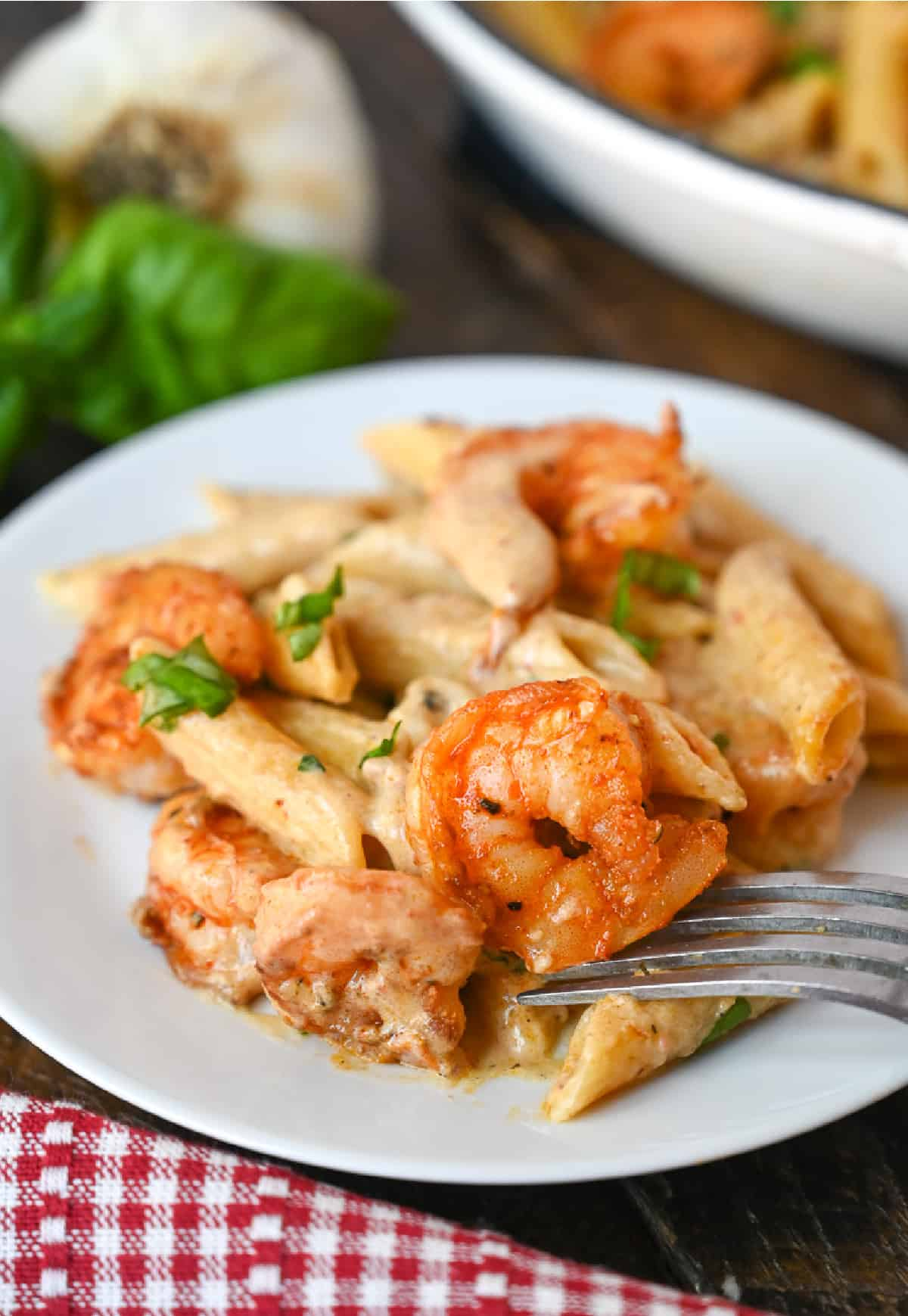 A serving of creamy garlic shrimp pasta on a white plate with a fork.