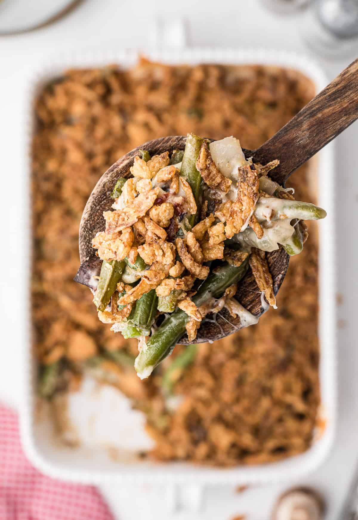 A wooden spoon scooping up a serving of green bean casserole.