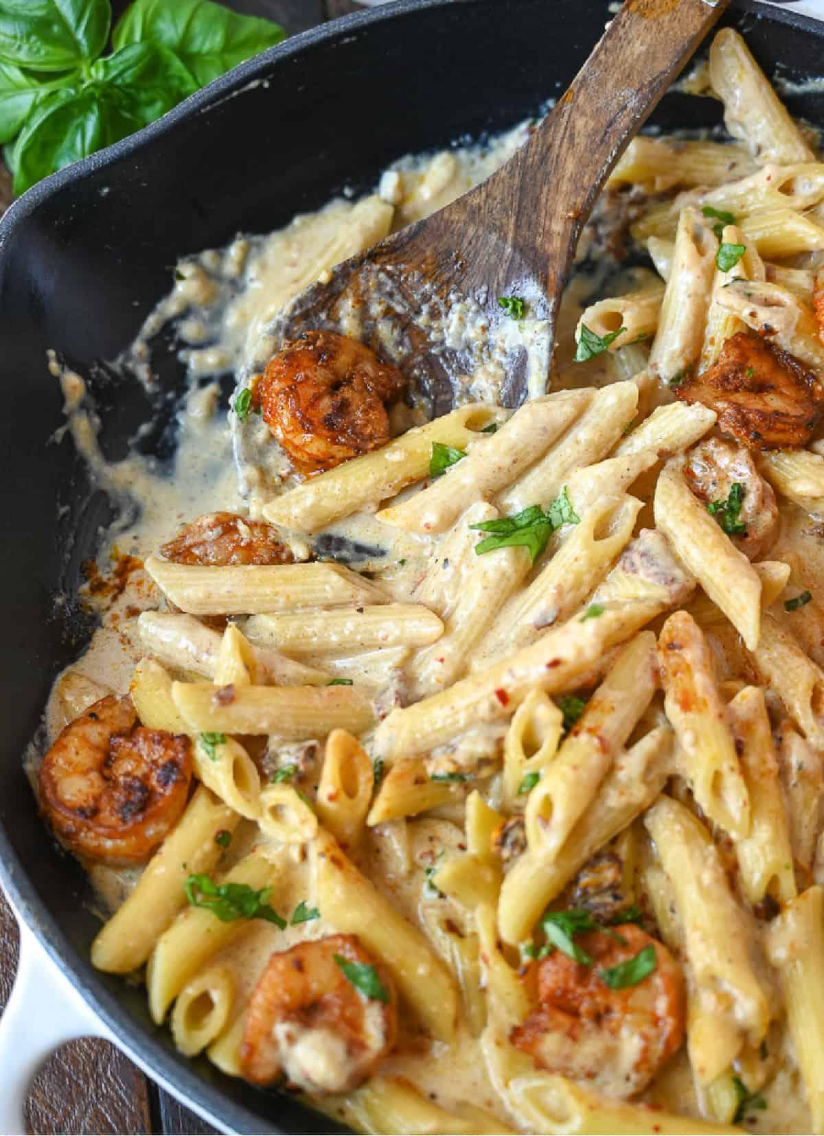Creamy garlic shrimp pasta in a skillet with a wooden spoon.