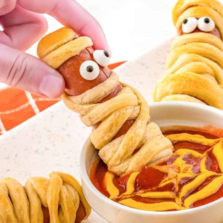 A mummy hotdog being dipped in a ketchup mustard web sauce.
