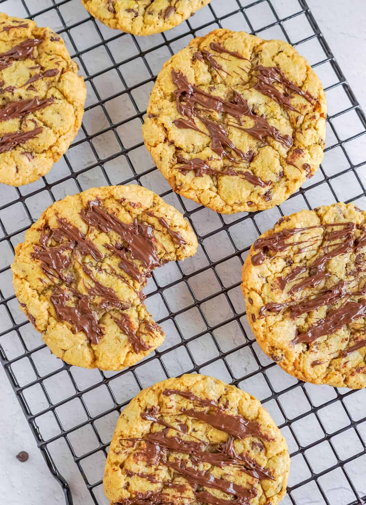 Pumpkin chocolate chip cookies on a cooling rack, one with a bite out of it.