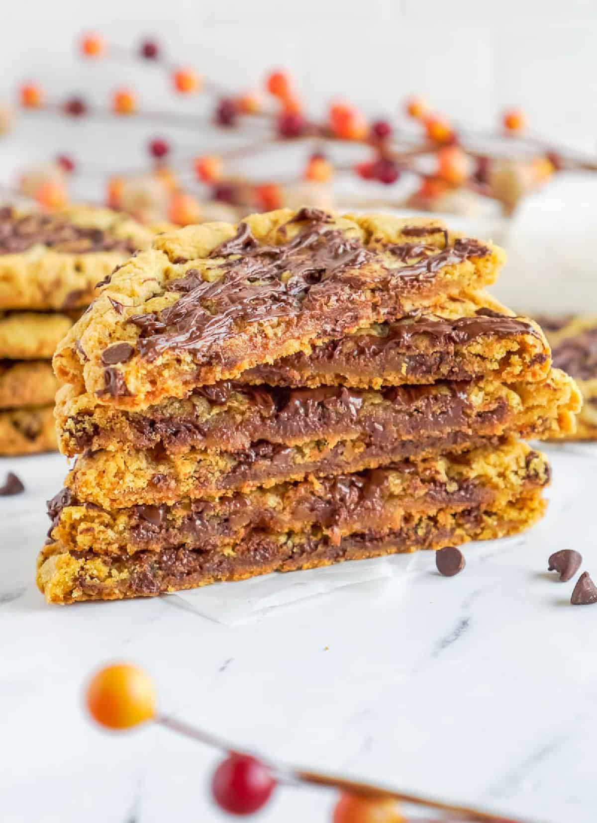 A stack of pumpkin chocolate chip cookies cut in half with melty chocolate.