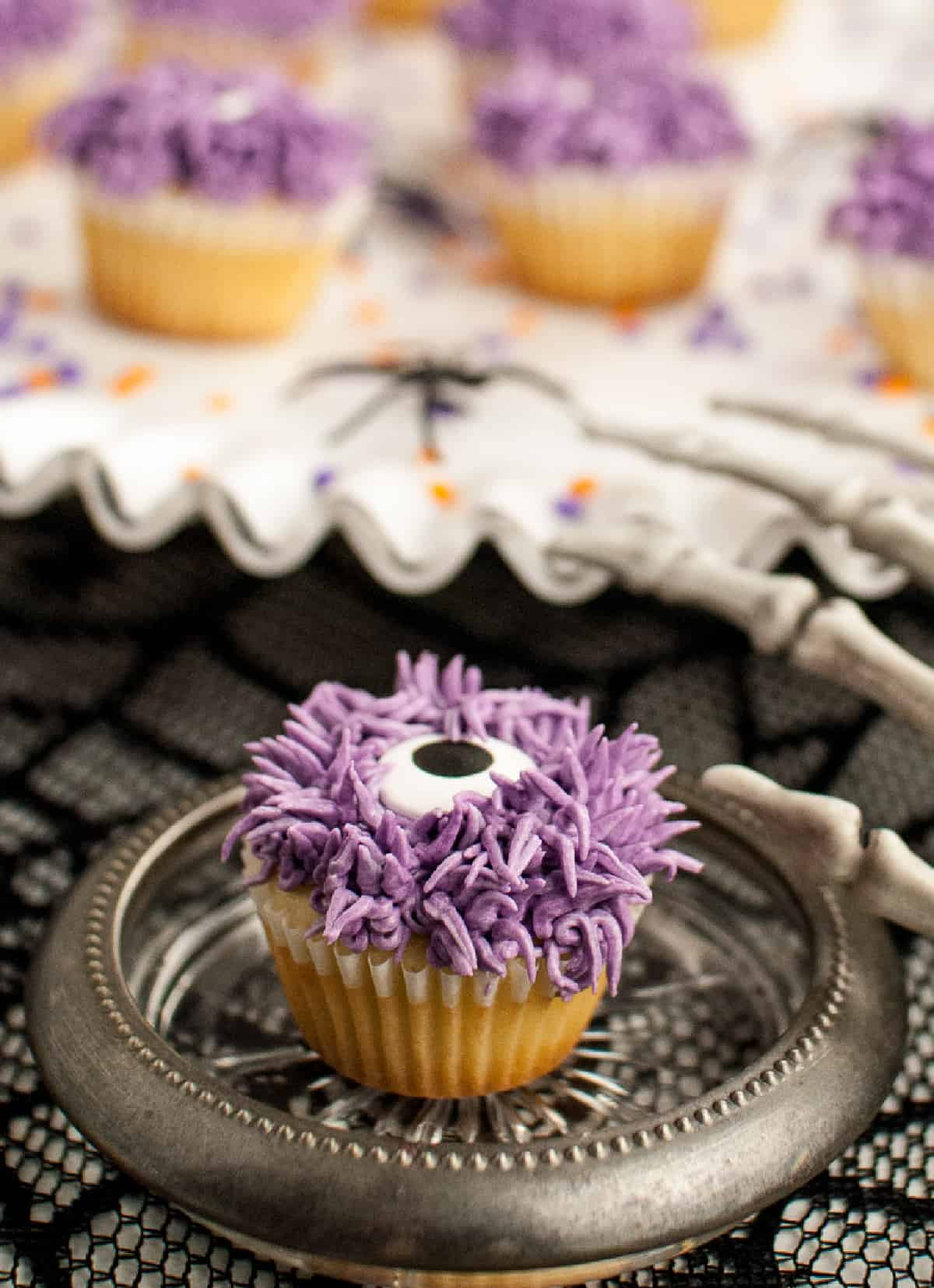 A purple monster cupcake on a small silver plate with a sceleton hand on the side.