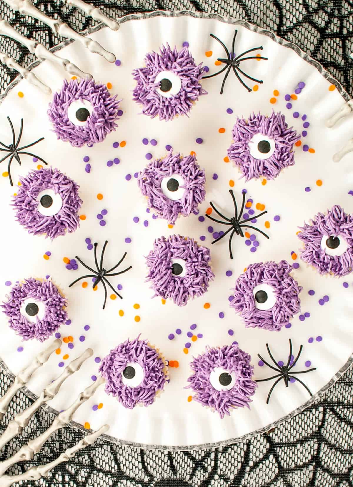 Purple monster cupcakes placed on a white platter with plastic spider scattered on the platter.