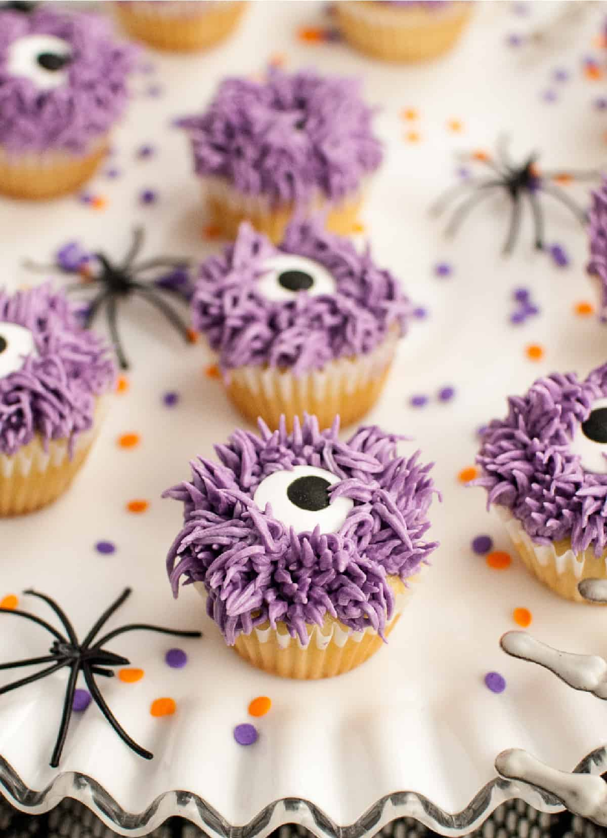 A close up photo of a purple monster cupcake on a white platter.