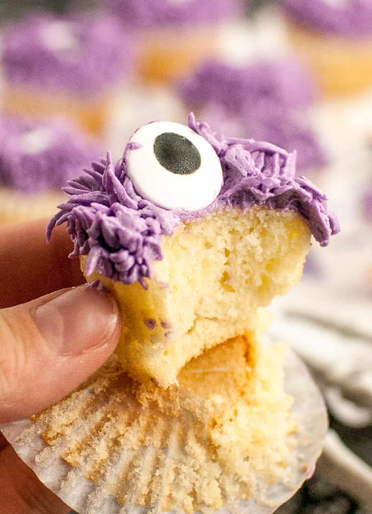A cmonster cupcake being held with a bite out of it.