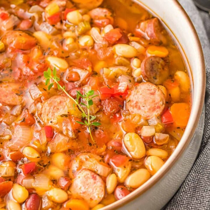 A close up photo of slow cooker sausage bean soup in a bowl.